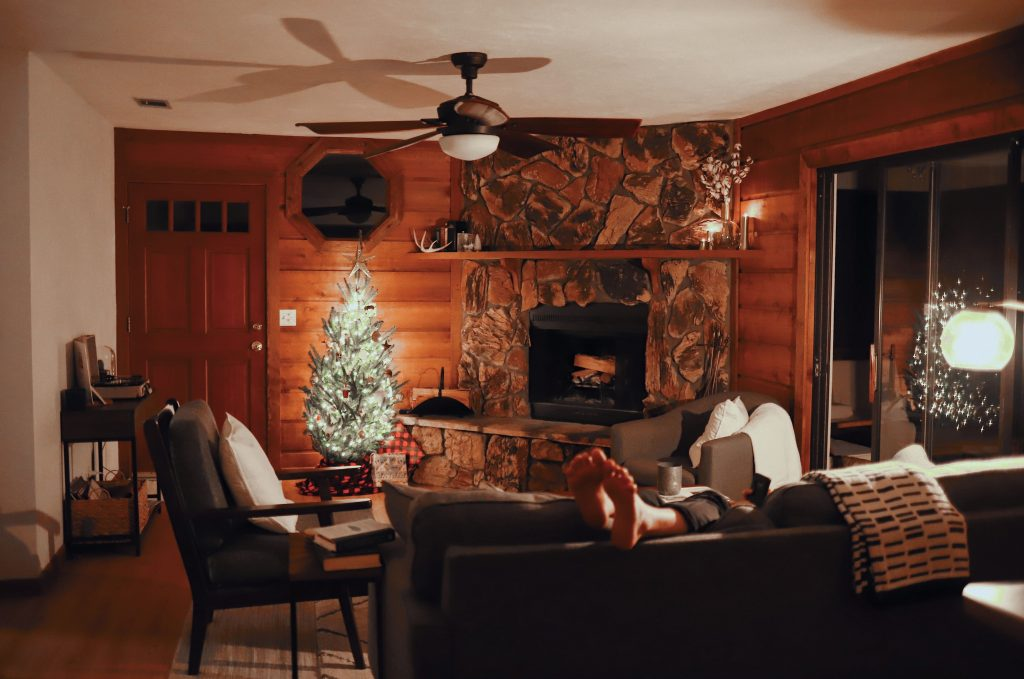 A cozy Christmas at home featuring the feet of a man draped over his couch with comfy throw blankets and a lit up Christmas tree by a fireplace in a wood paneled room.