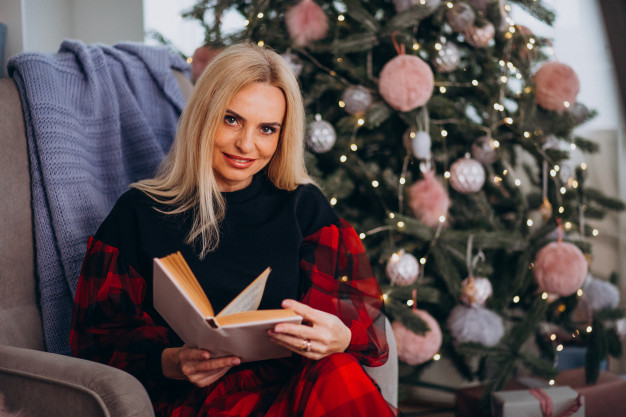 A woman sits neatly groomed and dressed up for Christmas in a comfy chair holding a book with a Christmas tree behind her.
