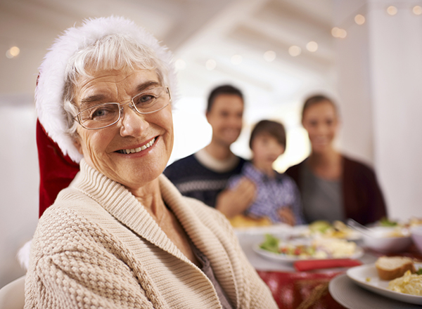 A senior woman smiles contentedly at the camera at a family holiday dinner.
