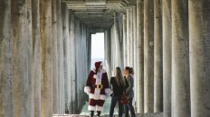 Two women meet Santa Clause under the dock at the beach for a CovidSafe Holiday